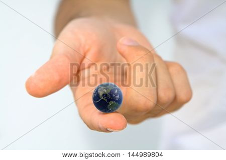 Hand holding earth on fingertip/ World at your Fingertips