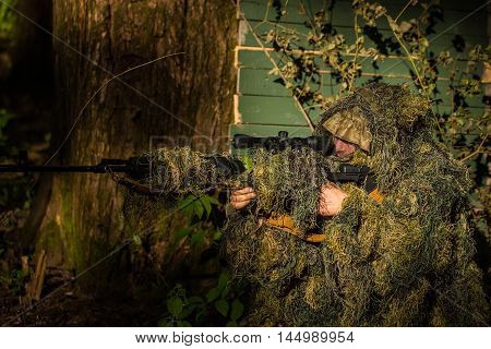 Sniper soldier in ghillie suit camo and mask sitting with rifle aiming target near tree and green branches background