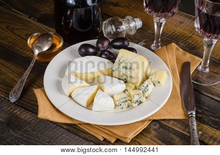 Cheese plate with grape and wine on a wood
