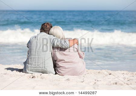Altes Paar sitzt am Strand