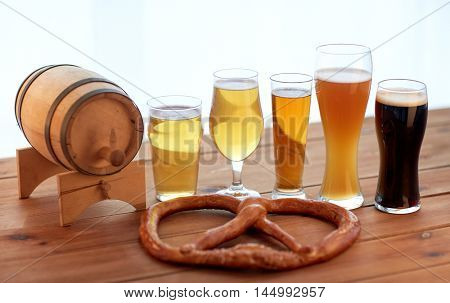 brewery, drinks and food concept - close up of different beer glasses, wooden barrel and pretzel on table