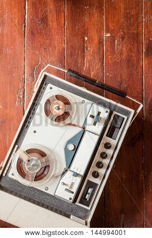 Old tape recorder on wooden background with natural lighting