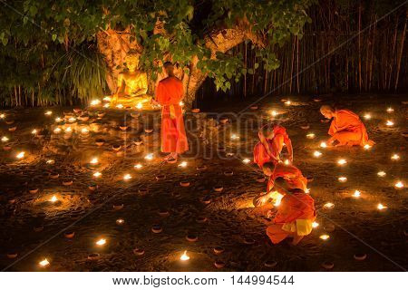 CHIANG MAI THAILAND - JULY 11: Unidentified Thai monks meditate around buddha statue among many lanterns at Phan Tao temple in Asalha Puja Day on July 11 2014 in Chiang Mai Thailand.