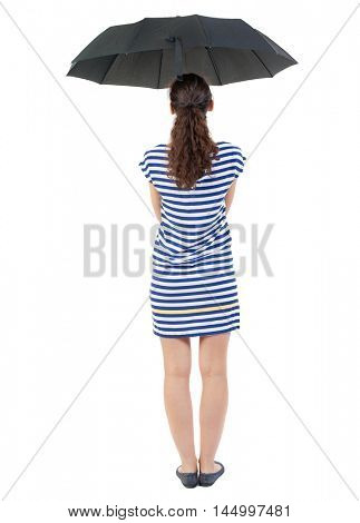 young woman in dress under an umbrella. Swarthy girl in a checkered dress standing under an umbrella.
