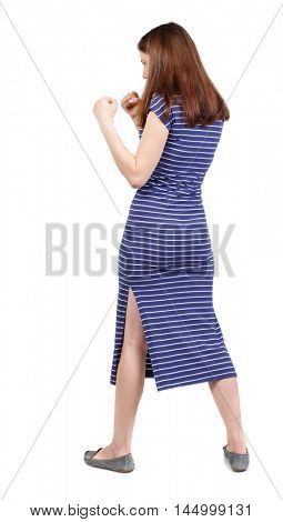 skinny woman funny fights waving his arms and legs. brunette in a blue striped dress standing sideways in a boxing rack.