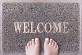 Welcome Door Mat With Female Feet. Friendly Grey Door Mat Closeup with Bare Woman Feet Standing. Welcome Carpet. Girl Feet with White Painted Toenails on Foot Scraper. poster