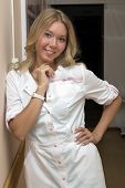 The blonde the nurse in a white dressing gown smiles standing in a hospital corridor poster