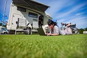 Woman on the grass with a dog looking at a laptop. Caravan car Vacation. Family vacation travel, holiday trip in motorhome poster