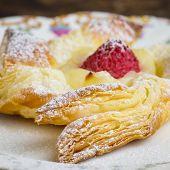 Homemade danish puff pastry pinwheels with vanilla pastry cream and raspberries and icing sugar poster