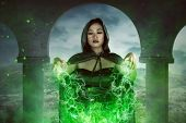 Asian witch woman casting spell with concentration the green light out from her hand poster