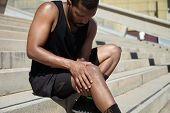 Handsome muscular male jogger wearing black training outfit touching his knee in pain with clasped hands having sprain or rupture in his muscles after exercising outdoors. Sports injury concept poster