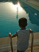 A small boy looking at the swimming pool at sunset poster
