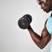 Side view shot of young and muscular african man doing biceps curl with dumbbell against grey background poster