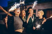 Group of friends enjoying out with sparklers on city street. Young people enjoying new years eve with fireworks. poster