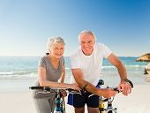 Retired couple with their bikes on the beach poster