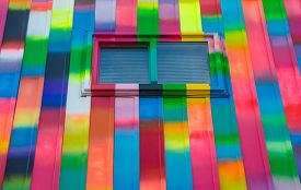 Abstract color, bright, rectangular, rainbow colored window and wall exterior.  Colorfully bright painted aluminum panelled wall featuring small slider window with blind shades drawn.