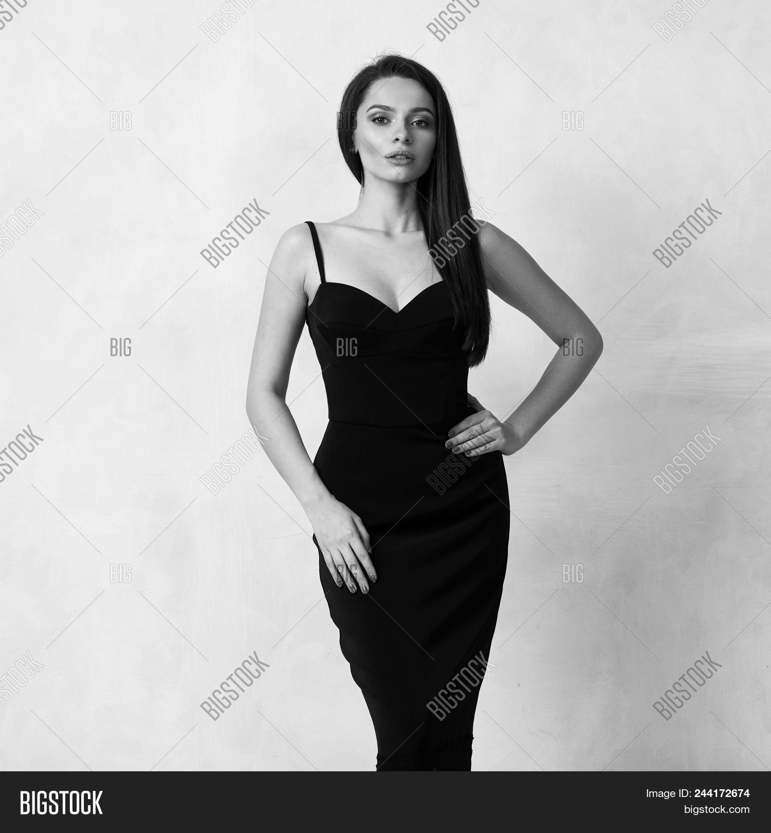 e40b4f7944 Beautiful Female Model With Long Brunette Hair Demonstrating Black Bodycon  Dress With Straps And Lac