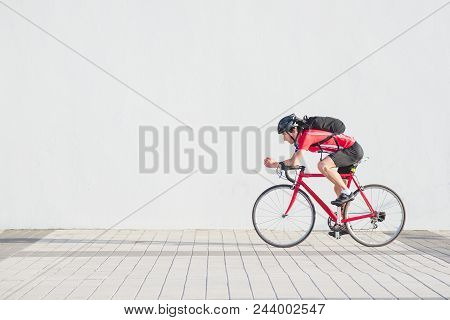 Side View Photo Of A Professional Cyclist In Red Sportswear And A Helmet Riding A Red Bike On A Whit