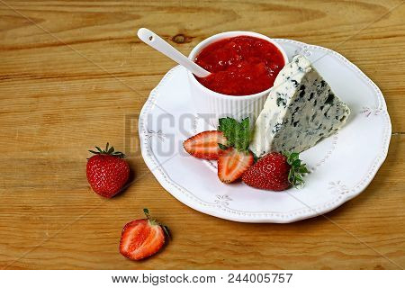 Cheese With A Noble Blue Mold On Plate With Strawberries And With Strawberry Sauce, Mint, On A Woode