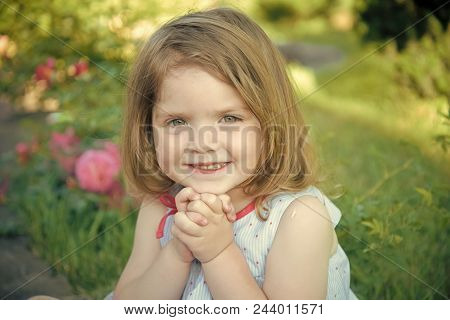 Future And Flourishing. Girl Smiling With Folded Hands In Summer Garden. Child Sitting At Blossoming