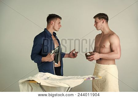 Brothers. Brotherly Help. Man Ironing Clothes With Iron On Board. Macho Eating Food. Healthy Dieting