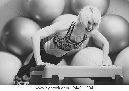 Endurance, strength and fitness concept. Girl in sportswear training on step platform in gym. Happy woman athlete do pushup on stepper. Sport, health, activity poster