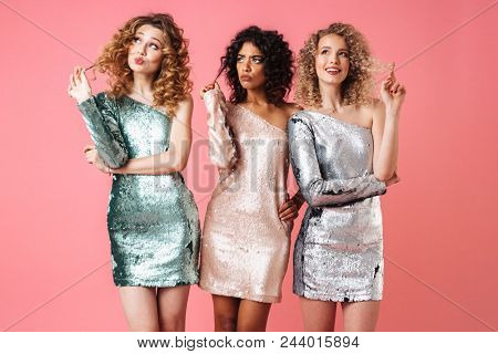 Three beautiful pensive women in shiny dresses looking away isolated over pink background