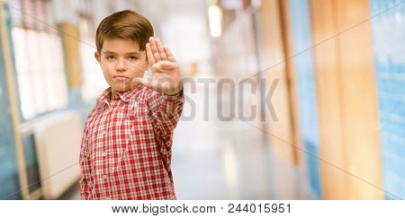 Handsome toddler child with green eyes annoyed with bad attitude making stop sign with hand, saying no, expressing security, defense or restriction, maybe pushing at school corridor