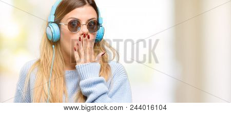Young woman listen to music with headphone covers mouth in shock, looks shy, expressing silence and mistake concepts, scared