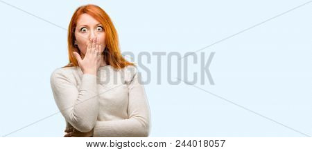 Beautiful young redhead woman covers mouth in shock, looks shy, expressing silence and mistake concepts, scared isolated over blue background