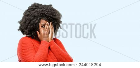 Beautiful african woman smiling having shy look peeking through her fingers, covering face with hands looking confusedly broadly, blue background