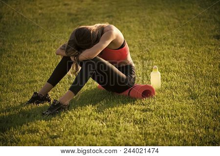 After A Workout. Tired Woman In Sportswear Relax After Workout, Training. Sportswoman Sit On Green G