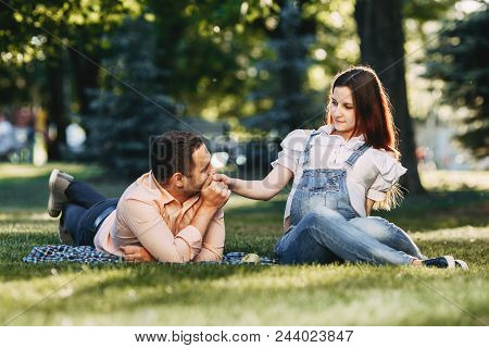 Outdoor Portrait Of Happy Family. Pregnant Couple Sitting At Park. Pregnancy, Family, Leisure, Mothe
