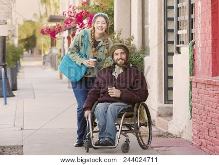 Woman With Friend In Wheelchair Holding Coffee