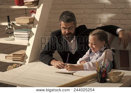 Home Schooling. Kid And Man Sit By Desk With School Supplies. Schoolgirl And Her Dad With Happy Face