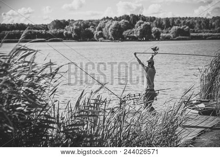 Fisherman Is Fishing On A Fishing Trip. Man Fish With Spinning Tackle On Wooden Pier.