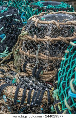 Crab And Lobster Pots With Fishing Equipment On The Harbour In Penzance, Cornwall, England
