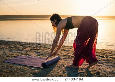 Woman On The Beach At Sunset Starts Yoga Training With Yoga Mat. Morning Natural Stretch Warm-up Tra