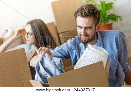 Smiling Man Looking Inside Of Carton Box With Stuff Moving With Girl To New Apartment And Unpacking.