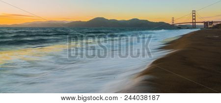 Whispers Of Wisdom: Wispy Waves, Flowing Up Onto Baker Beach Overlooking Sunset At Golden Gate Bridg