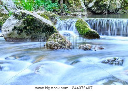 Beautiful Scene Of Waterfall With Stone Cascade And Large Rocks Covered With Moss, Close Up