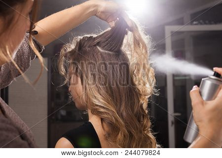 Back View Of Professional Hairdresser Fixing A Coiffure With Curls Of A Young Client Using A Hair Sp