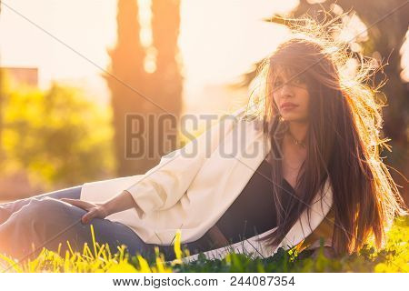 Backlight Portrait Of A Woman Lying In The Park At Sunset