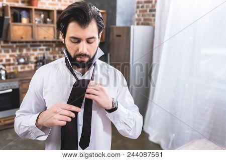 Handsome Loner Businessman Tying Necktie At Home