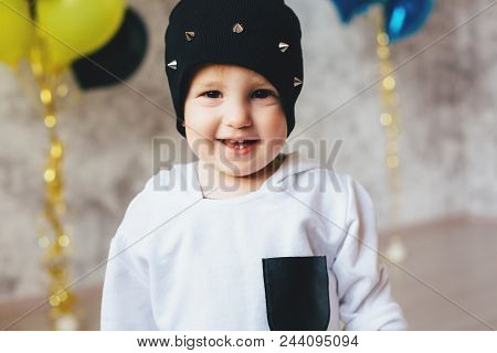 Happy Toddler Boy In A In A White Sweatshirt And A Cap With Spikes On White Background With Festive