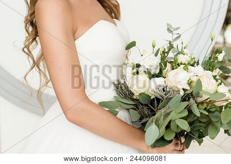 Beautiful Bride In White Dress Holding Lush Wedding Bouquet Of Roses And Eucalyptus Greenery Indoors