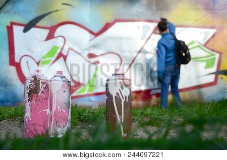 A Few Used Paint Cans Against The Background Of The Space With The Wall On Which The Young Guy Draws