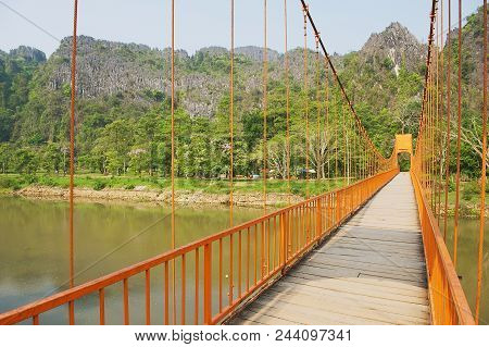 Vang Vieng, Laos - April 21, 2012: Suspension Footbridge Over The Nam Song River With The Scenic Lim