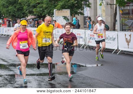 Dnipro, Ukraine - May 20, 2018: Three Friends (1 Male And Two Females) Running Together On The Centr