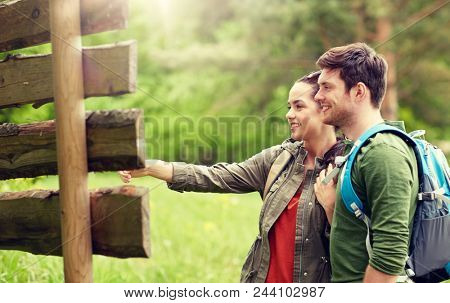 adventure, travel, tourism, hike and people concept - smiling couple with backpacks looking at signpost outdoors